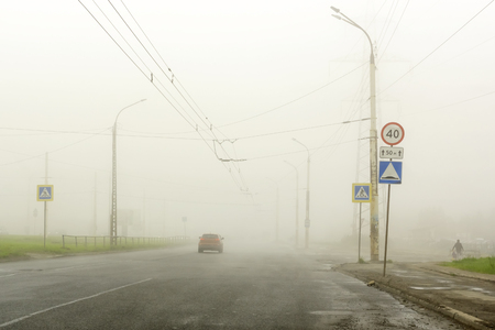 Dense fog in the summer in the city on the highway