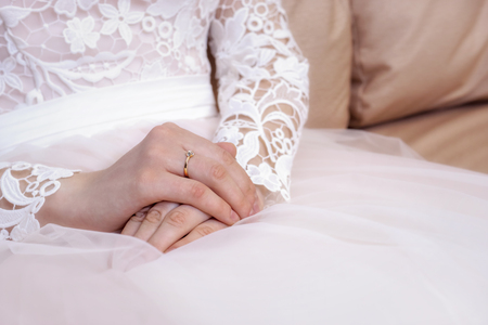 Hands of the bride in white and pink wedding dress