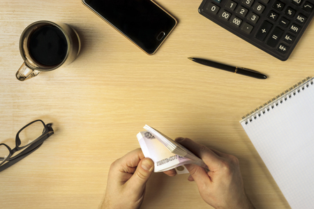Hands counting profit money in business space