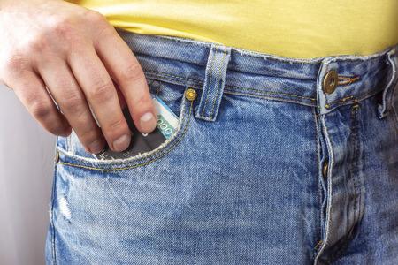 Hand puts cash money in pocket