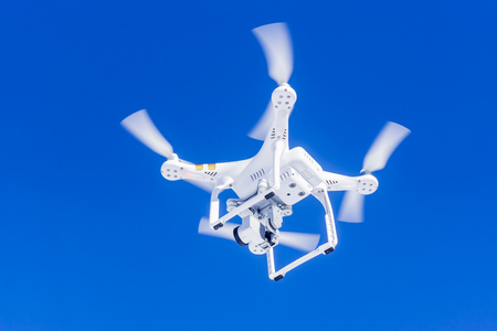 White quadcopter in clear blue skies Stock Photo