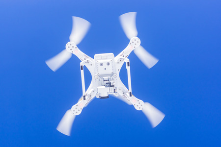 Graceful snow white quadcopter in clear blue sky Stock Photo