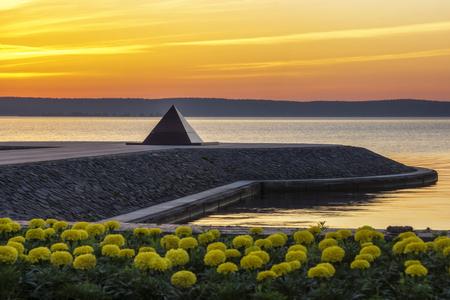 Serene sunrise on city embankment of lake