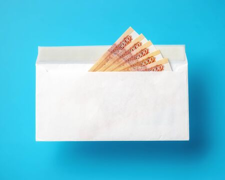 White envelope with cash ruble banknotes on light blue background