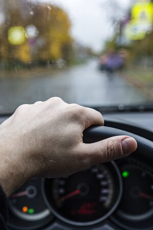 Hand of driver on steering wheel in city in rainy weather Archivio Fotografico