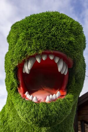 Tyrannosaurus head with open mouth covered with artificial green grass