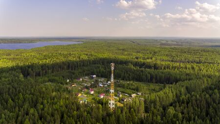 Aerial view of village with a radio mast in wilds of summer forest