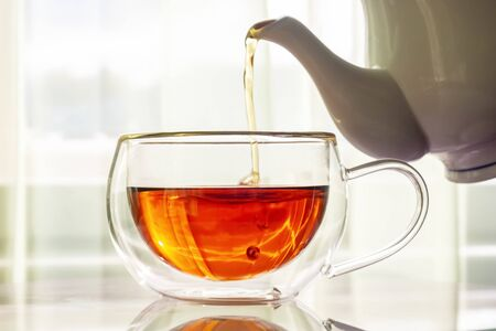 Fragrant strong tea pours from teapot spout in cup on table