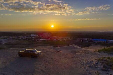 Retro Soviet car on sandy hill at beautiful summer sunset
