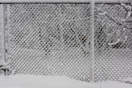 Background of fence mesh netting backdrop in heavy snow in winter
