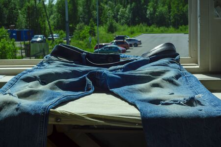 Blue denim jeans with trendy scuffs and holes on windowsill on summer day Фото со стока