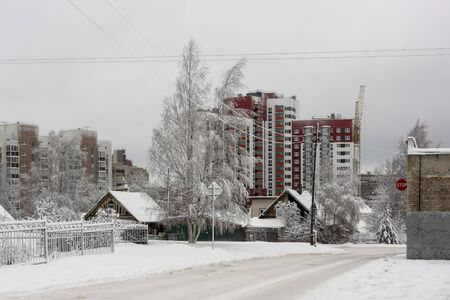 Old wooden houses on background of new tall city houses in winter