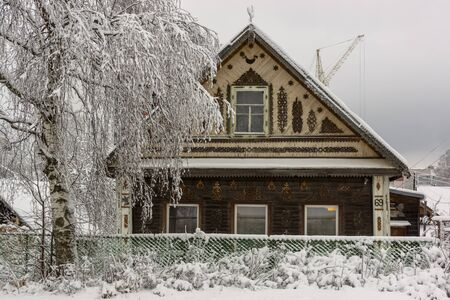 Old decorated traditional wooden house in Russian city in winter