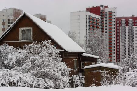 Old wooden house against the background of new tall city houses in winter Фото со стока