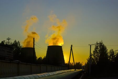 Smoke from huge pipes of city thermal power plant in sunset sky Фото со стока