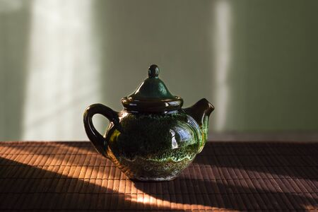 A small teapot for tea brewing on table in sunlight