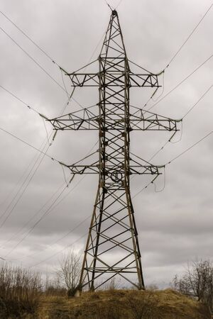 High-voltage mast with electric cables on hill, vertical format