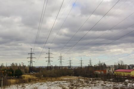 Industrial scene of high-voltage masts with electric cables through the skies