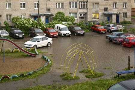 Cars in city yard stand in puddle on playground during summer rain Фото со стока