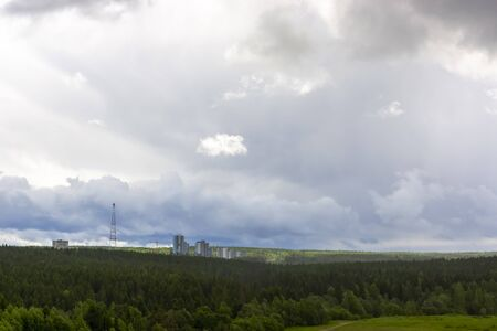 High buildings of city on hill among pine forest in natural landscape