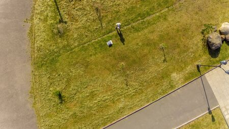 Top view on drone pilot on the lawn in city park