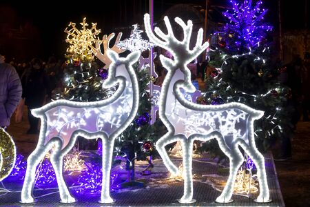 Wonderful holiday illumination of deer figures sparkling with bokeh lights Фото со стока