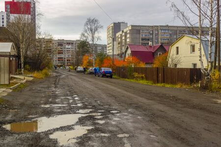Old wooden houses and broken road on city street in autumn