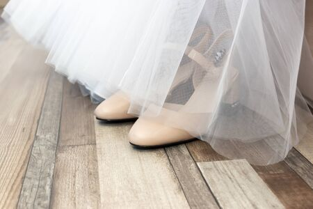 Behind the fabric hem of wedding dress are the bride's wedding shoes Reklamní fotografie
