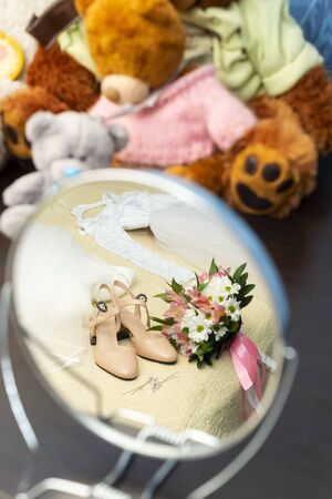 Wedding dress, shoes and bridal bouquet are in mirror near of teddy bears