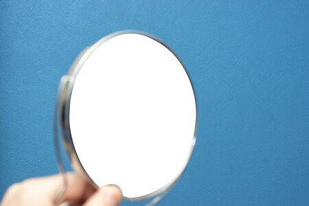 Round hand mirror with isolated reflection on textured blue wall background