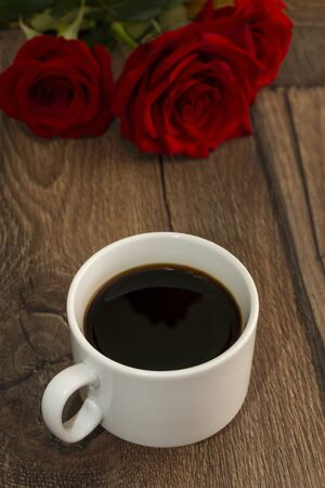 Romantic bouquet of red roses on a wooden table and a cup of coffee, vertical