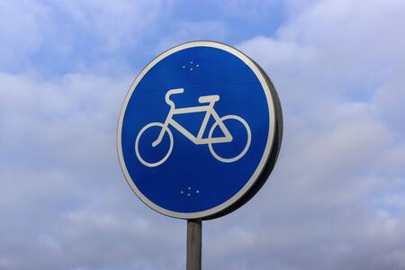 Road sign with a bicycle on a blue background indicates a bicycle path Banco de Imagens