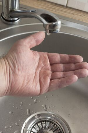 A drop of water drips in mans palm who checks if there is water in kitchen tap Stok Fotoğraf