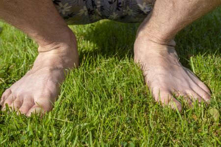 Bare feet of man in shorts squatted on lush grass on lawn in summer