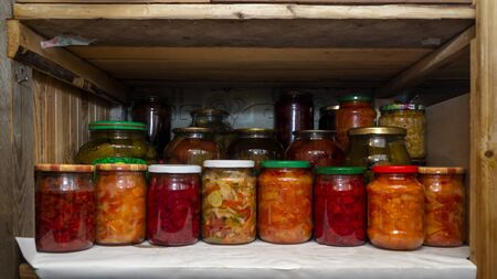Wooden shelf in pantry with provisions in glass jars with pickled vegetables
