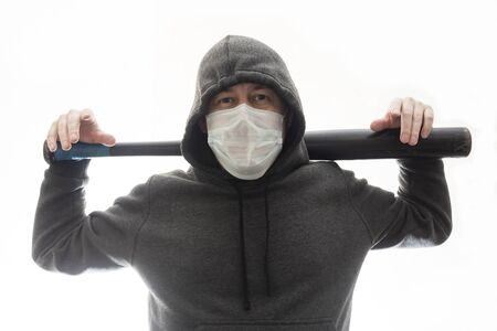 A confident man in hoody and mask with black baseball bat on his shoulders Фото со стока