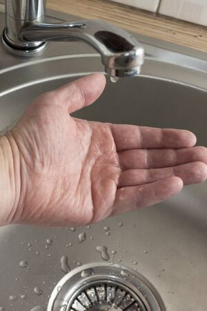Drops of water drip in mans palm who checks if there is water in kitchen tap