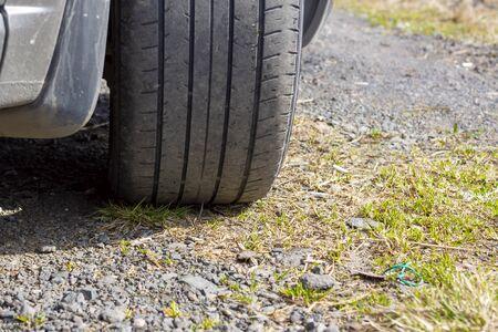 Shabby rubber tire of car wheel on gravel road during a summer trip Reklamní fotografie