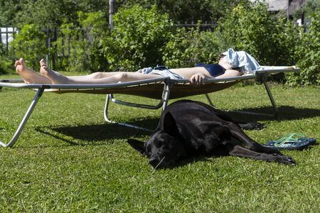 Girl on hot summer day sunbathes on a lawn on cot and next lies black shepherd