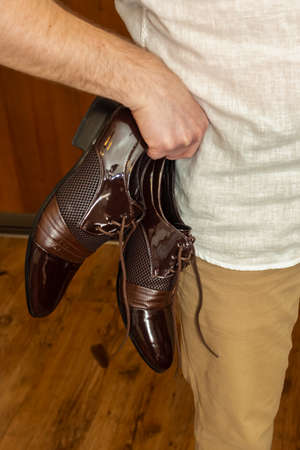 Chic man shoes in hand of a man who stands in thought