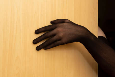 Hand in black nylon glove on door of room entices into a sweet trap