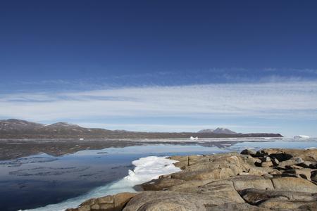 lejos: Hermosa vista de la bahía en Qikiqtarjuaq con las montañas en el fondo, isla de Broughton, Nunavut Canadá Foto de archivo