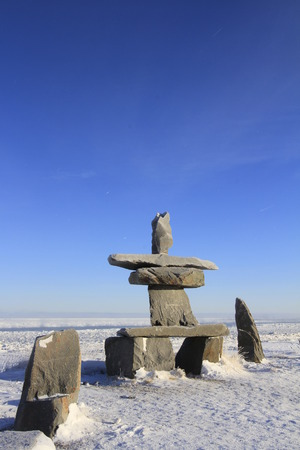 Inukshuk (Inuksuk) found near Churchill, Manitoba with snow on the ground in early November, Canada
