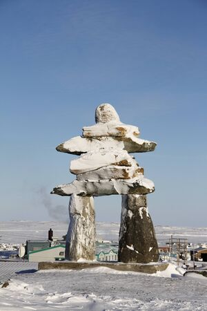 Inuksuk or Inukshuk landmark covered in snow found on a hill in the community of Rankin Inlet, Nunavut, Canada