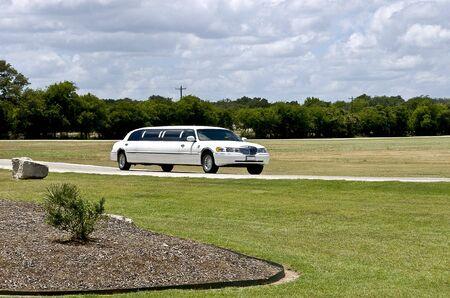Stretch limo driving down a private drive Banco de Imagens