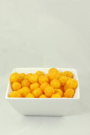 puffs: A delicious bowl of cheese puffs to eat.