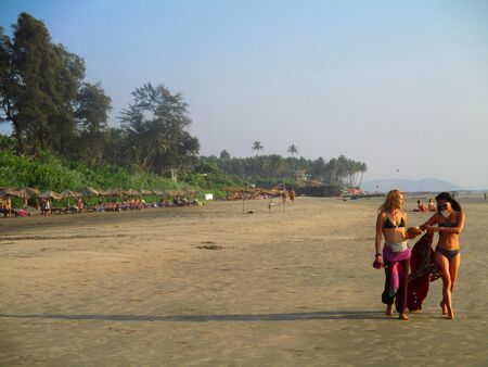 backpackers: Two female backpackers walking along the beach in Goa Editorial