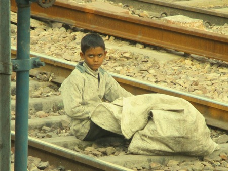 homeless children: Homeless child in Agra, India, collecting recycling from between the train tracks