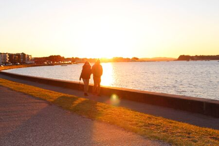 refelction: A couple walking hand in hand along the coast in Sandbanks, Dorset