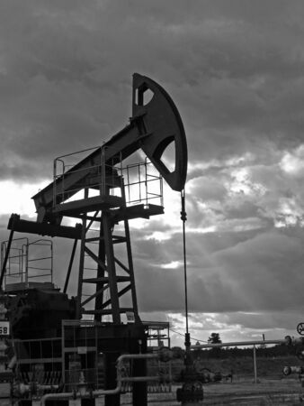 Oil sunset. Pump in beams. Stock Photo